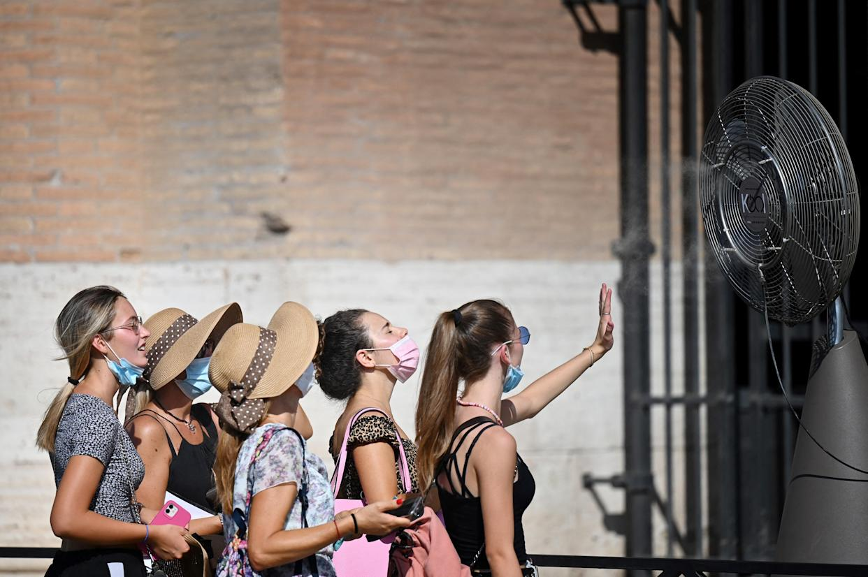 TOPSHOT - A group of women cool off in front of a cooling fan during a heatwave as they queue at the entrance of the Colosseum in Rome on August 12, 2021. - An anticyclone dubbed Lucifer is sweeping across Italy, sending temperatures soaring and causing what is believed to be a new European record of 48.8 degrees Celsius (119.8 Fahrenheit) in Sicily on August 11. (Photo by Alberto PIZZOLI / AFP) (Photo by ALBERTO PIZZOLI/AFP via Getty Images)