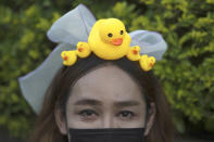 A protester wears a head band designed with yellow ducks, which have become good-humored symbols of resistance during anti-government rallies, on Wednesday, Nov. 25, 2020, in Bangkok, Thailand. Thai authorities have escalated their legal battle against the students leading pro-democracy protests, charging 12 of them with violating a harsh law against defaming the monarchy. (AP Photo/Wason Wanichakorn)