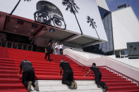 FILE - In this July 6, 2021 file photo Crew members install the red carpet at the Palais des Festival ahead of the opening day of the 74th international film festival, Cannes, southern France. The Cannes Film Festival returned this month, rolling out the red carpet and restoring glamour to the French Riviera with a collection of provocative films and a parade of stars. (AP Photo/Brynn Anderson, File)
