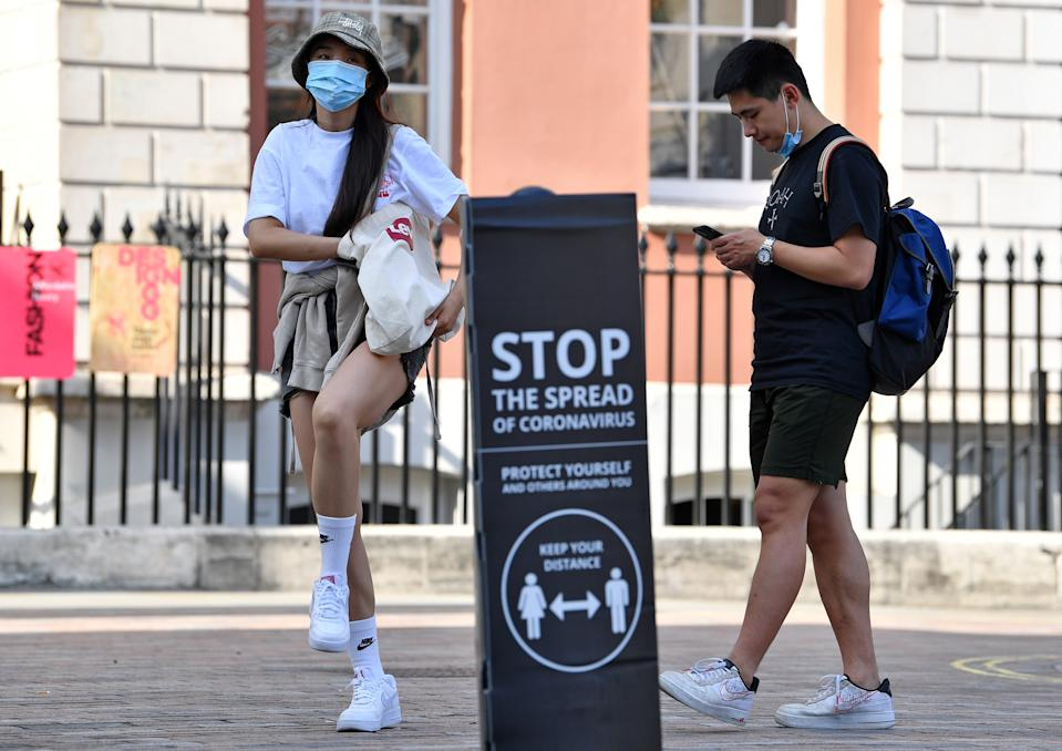 """People wearing a face mask or covering due to the COVID-19 pandemic, stand near a sign reading """"Stop the spread of Coronavirus"""" in Covent Garden, London on September 22, 2020. - The British government announced fresh steps Tuesday to try and stop a coronavirus surge in England, as the World Health Organization warned that new cases worldwide soared to almost two million last week in a grim new record. The measure included early closing time for pubs and restaurants, a resumption of advice for people to work from home, coupled with new penalties for breaking the rules. (Photo by Ben STANSALL / AFP) (Photo by BEN STANSALL/AFP via Getty Images)"""