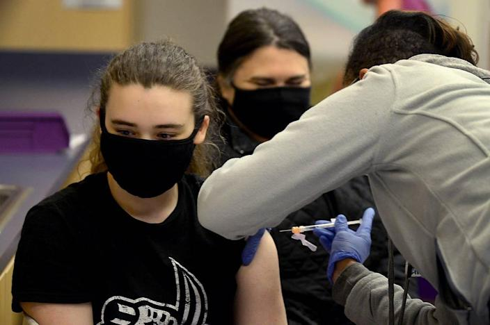 Elise Arnold, 15 years, left, receives her first COVID vaccination shot on Wednesday, May 12, 2021 at the Novant Health clinic at 6070 East Independence Blvd. Looking on in the background is EliseÕs mother, Charity Arnold.