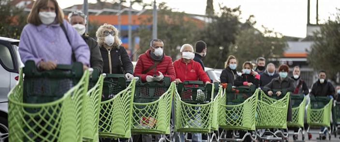 lineup of shoppers at supermarket with grocery carts