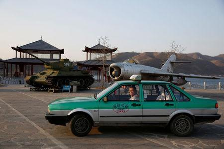 A taxi is parked in front of retired airplane and tank on display, at a Chinese village bordering North Korea at Dandong in China's Liaoning Province, April 13, 2017. REUTERS/Aly Song