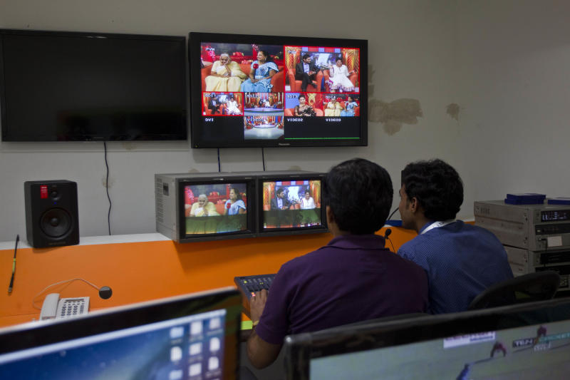 In this July 26, 2013 photo, employees monitor TV screens showing a talk show on Shagun TV, at itsstudio in Noida, India. Indians are obsessed with weddings and obsessed with reality television. Now Shagun TV, a new television channel headquartered in a sprawling suburb of India's capital, is hoping it has found a can't-miss idea — merging the two into a 24-hour matrimonial TV station.(AP Photo/Tsering Topgyal)