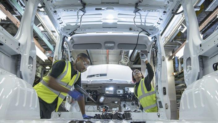 Car workers wearing high visibility jackets fitting parts on vehicle on production line in car factory