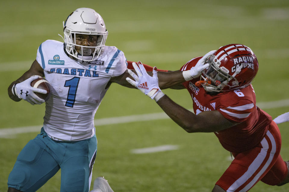 Coastal Carolina running back CJ Marable (1) stiff arms Louisiana-Lafayette safety Percy Butler (9) during an NCAA football game on Wednesday, Oct. 14, 2020 in Lafayette, La. (AP Photo/Matthew Hinton)