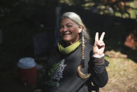 """Gina """"Mama G"""" Prince, of Florida, poses for a photo on Friday, July 2, 2021, in the Carson National Forest, outside of Taos, N.M. Prince said she was counting the days when she could return to the Rainbow Gathering, and annual July 4th celebration held in a different state each year. (AP Photo/Cedar Attanasio)"""