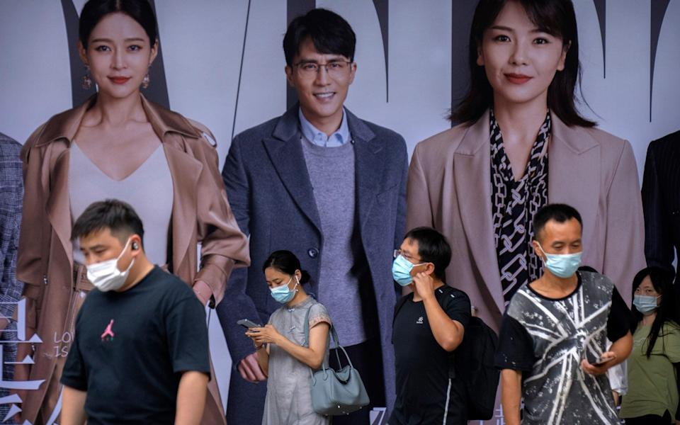 During the morning rush hour in Beijing, people wearing face masks walk past billboards amid China's worst Covid surge in months - Mark Schiefelbein/AP