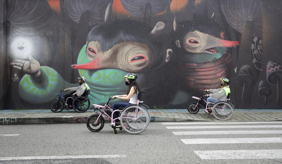 Martin Londoño, left, owner of MATT, an electric wheelchair tour company, rides with some of his clients during a tour in Medellin, Colombia, Wednesday, Nov. 18, 2020. The steering and breaks on the wheelchairs are like those on a regular bicycle, while accelerating only requires pushing a button on one of the handles. (AP Photo/Fernando Vergara)