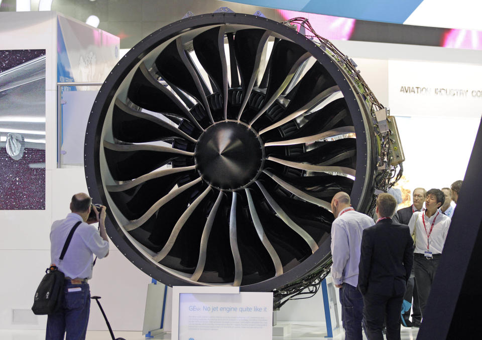"""Visitors watch General Electric's turbo fan """"the GEnx engine, powering Boeing 787 Dremliner, during the 50th Paris Air Show at Le Bourget airport, north of Paris, Wednesday June 19, 2013. (AP Photo/Remy de la Mauviniere)"""