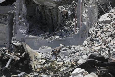A Houthi militant scavenges for usable ammunition from the remains of a destroyed supply truck at the yard of the residence of the military commander of the Houthi militant group, Abdullah Yahya al Hakim, after an airstrike, in Sanaa April 28, 2015. REUTERS/Khaled Abdullah