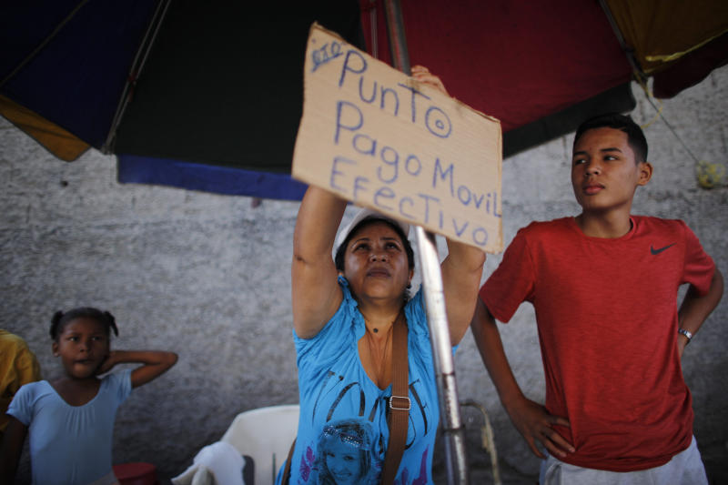 """In this Oct. 5, 2019 photo, Daixy Aguero puts up a sign that reads in Spanish """"Point of sale, mobile payment and cash,"""" at her stand where she sells beauty products, at a market in Caracas, Venezuela. It's a side-gig that allows her to keep her dream job as a preschool teacher. (AP Photo/Ariana Cubillos)"""
