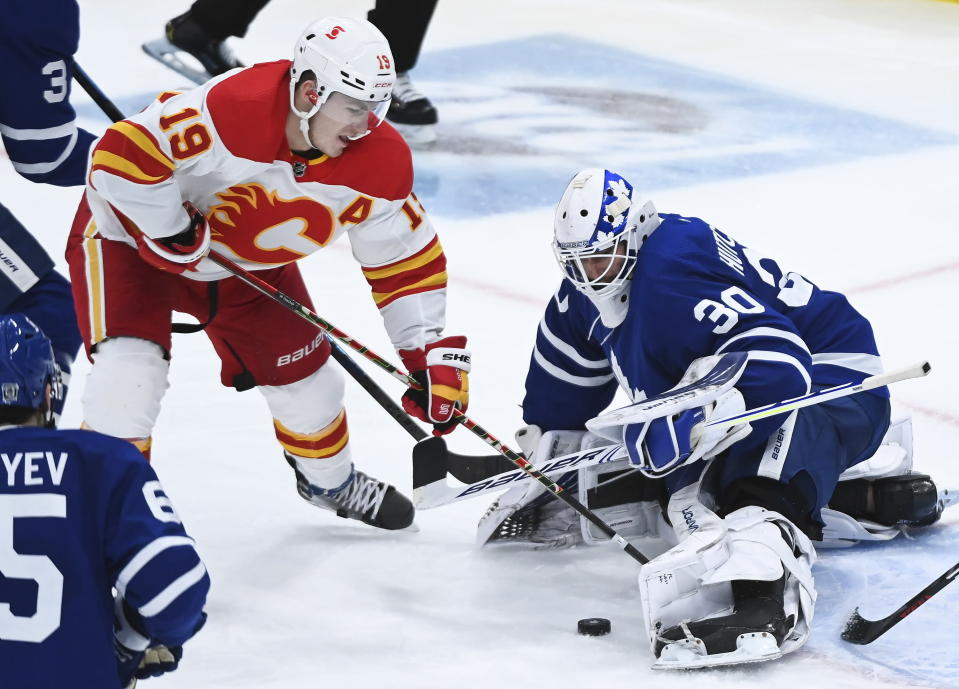 Toronto Maple Leafs goaltender Michael Hutchinson (30) makes a save as Calgary Flames left wing Matthew Tkachuk (19) digs out the rebound during the third period of an NHL hockey game in Toronto on Monday, Feb. 22, 2021. (Nathan Denette/The Canadian Press via AP)