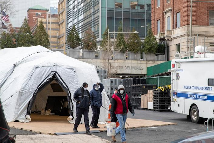 Medical Examiner personnel and construction workers are seen at the site of a makeshift morgue being built in New York, Wednesday, March 25, 2020: AP