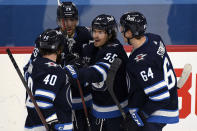 Winnipeg Jets' Mark Scheifele (55) celebrates his goal against the Vancouver Canucks with Jordie Benn (40), Blake Wheeler (26) and Logan Stanley (64) during the second period of an NHL hockey game Tuesday, May 11, 2021, in Winnipeg, Manitoba. (Fred Greenslade/The Canadian Press via AP)