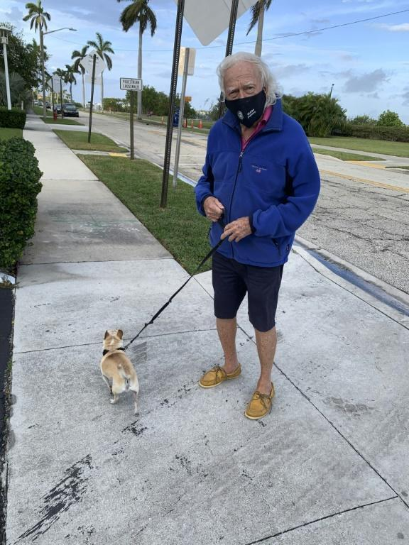 """Roger Everingham of Palm Beach, Florida, walks his dog Louie on December 24, 2020; the Joe Biden supporter has grown frustrated by what he calls the """"circus"""" that surrounds visits to the area by Donald Trump"""