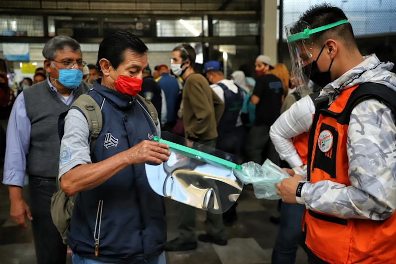 MEXICO CITY, MEXICO - JUNE 29: A Metro passenger receives a face shield donated by the government on June 29, 2020 in Mexico City, Mexico. As ICU occupancy trends downward, authorities downgraded the alert level from red to orange in Mexico City. Economic activity starts reopening gradually following a staggered schedule, with restrictions and preventive measures. (Photo by Agencia Press South/Getty Images)