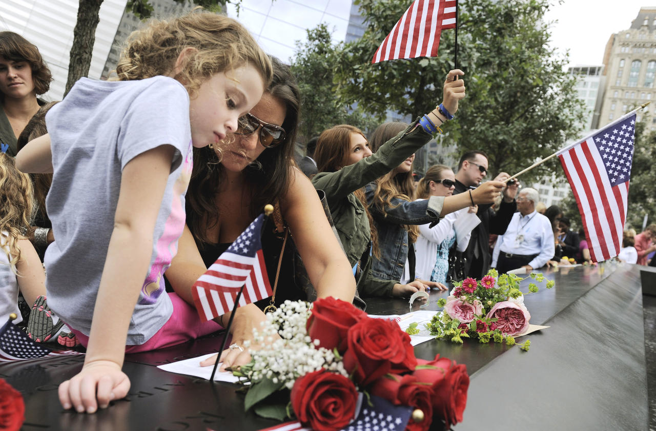 Elle Jackman,6, helps her mother, Iris Jackman, do a rubbing of her aunt's name, Brook Alexander Jackman, on the wall of the north pool of the Sept. 11 memorial during 10th anniversary observance of the terrorist attacks at the World Trade Center, Sunday, Sept. 11, 2011, in New York. (AP Photo/Justin Lane, Pool)