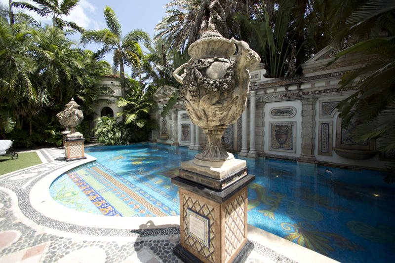 Decorative artwork stands in front of the 55 foot long swimming pool at the Versace mansion on Miami Beach, Fla., Tuesday, July 23, 2013. Though the Versace family hasn't owned the oceanfront mansion since 2000, auctioneers hope the Italian designer's legacy will attract bidders to the Miami Beach property when it goes up for auction Sept. 17. Gianni Versace was fatally shot on the mansion's stone front steps in 1997 by serial killer Andrew Cunanan. (AP Photo/J Pat Carter)