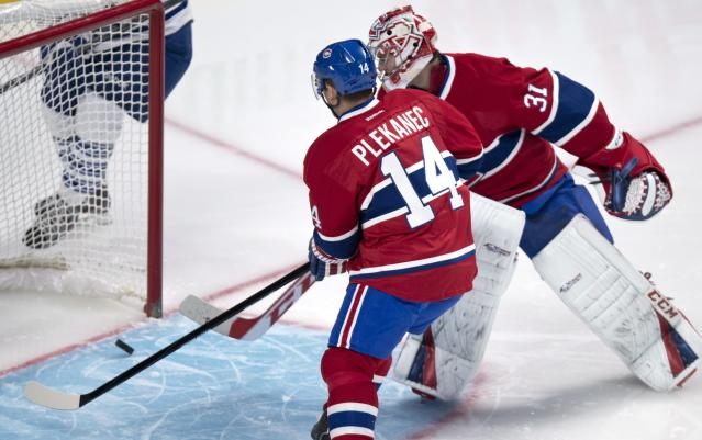 Montreal Canadiens goalie Carey Price and Tomas Plekanec watch the puck deflect off the goalpost as they face the Toronto Maple Leafs during the second period of an NHL hockey game Saturday, Nov. 30, 2013 in Montreal. (AP Photo/The Canadian Press, Paul Chiasson)