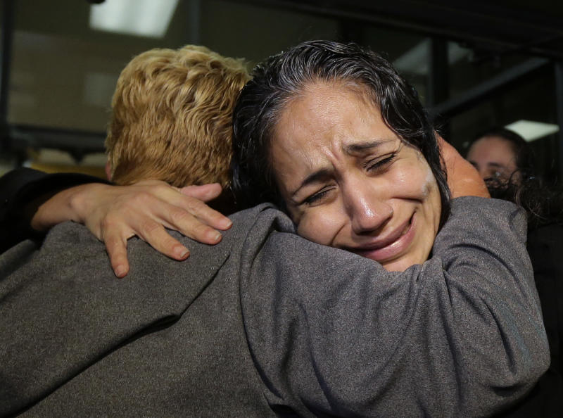 Cassandra Rivera, right, is greeted by family members after she, Elizabeth Ramirez and Kristie Mayhugh were released from the Bexar County Jail, Monday, Nov. 18, 2013, in San Antonio, after it was announced earlier in the day the women imprisoned for sexually assaulting two girls in 1994 were allowed to walk free after a judge agreed that their convictions were tainted by faulty witness testimony. (AP Photo/Eric Gay)