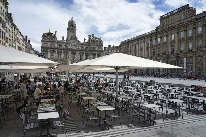 People eat and drink outdoors at a terrace bar in Lyon, central France, Tuesday, July 13, 2021. Nearly 1 million people in France made vaccine appointments in a single day, as the president cranked up pressure on everyone to get vaccinated to save summer vacation and the French economy. (AP Photo/Laurent Cipriani)
