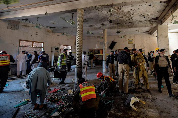Security officials examine the site of a blast at a religious school in Peshawar on Tuesday morning (AFP via Getty Images)