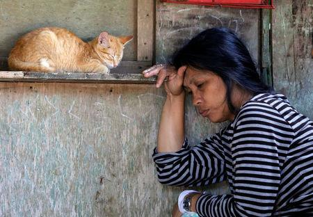 A woman displaced by fighting between government soldiers and Maute group rests near a cat at a makeshift evacuation centre in Marawi City, southern Philippines.   REUTERS/Erik De Castro