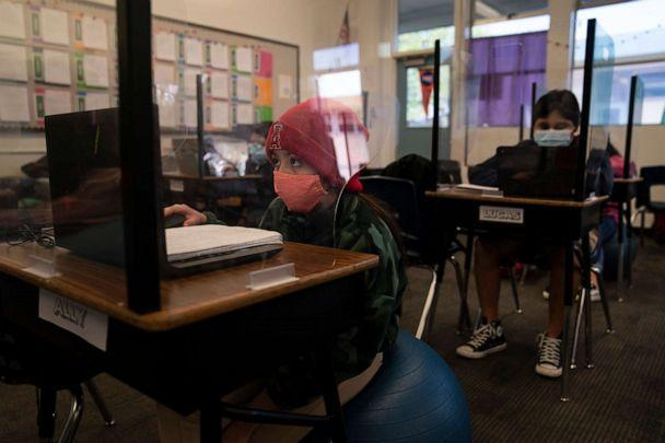 Fifth grader Ally Cortez works on her computer at West Orange Elementary School surrounded by a plastic shield in Orange, California, on March 18, 2021.  (Jae C. Hong/AP)