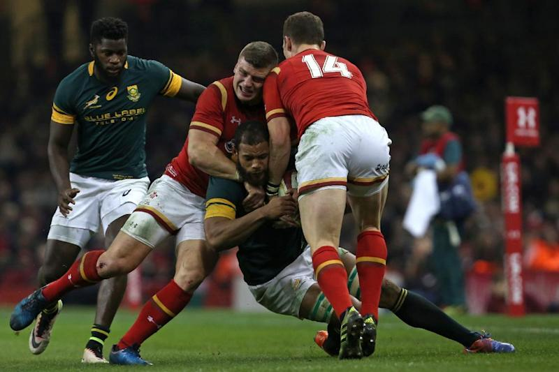 South Africa's flanker Nizaam Carr is tackled by Wale's centre Scott Williams and Wales' wing George North (R) during the rugby union test match between Wales and South Africa at the Principality stadium in Cardiff, south Wales, on November 26, 2016. (AFP Photo/Geoff CADDICK)