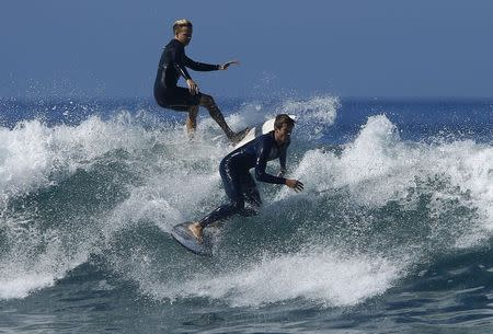 Surfers come close to colliding as they gather off the shore of Solana Beach, California to catch waves being generated out in the Pacific Ocean by Hurricane Marie August 27, 2014. REUTERS/Mike Blake