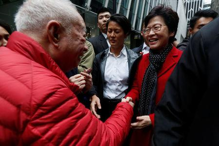 A man shakes hands with Carrie Lam, chief executive-elect, a day after she was elected in Hong Kong