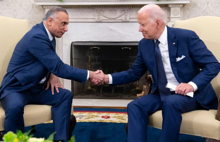 US President Joe Biden shakes hands with Iraqi Prime Minister Mustafa Al-Kadhimi (L) in the Oval Office of the White House.