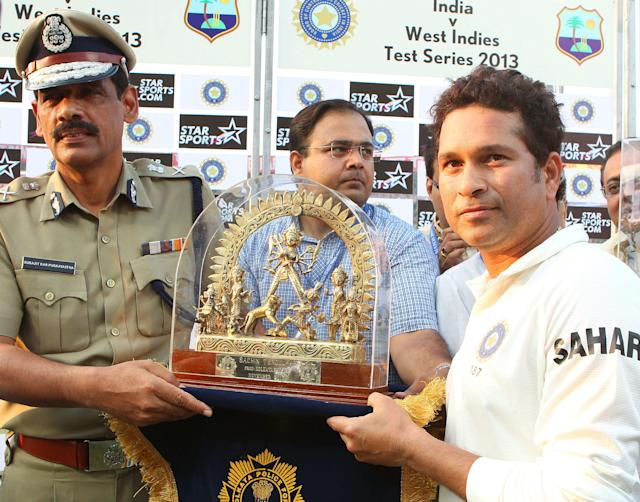 Sachin Tendulkar of India is presented with a memento by the commissioner of police during day three of the first Star Sports test match between India and The West Indies held at The Eden Gardens Stadium in Kolkata, India on the 8th November 2013 Photo by: Ron Gaunt - BCCI - SPORTZPICS