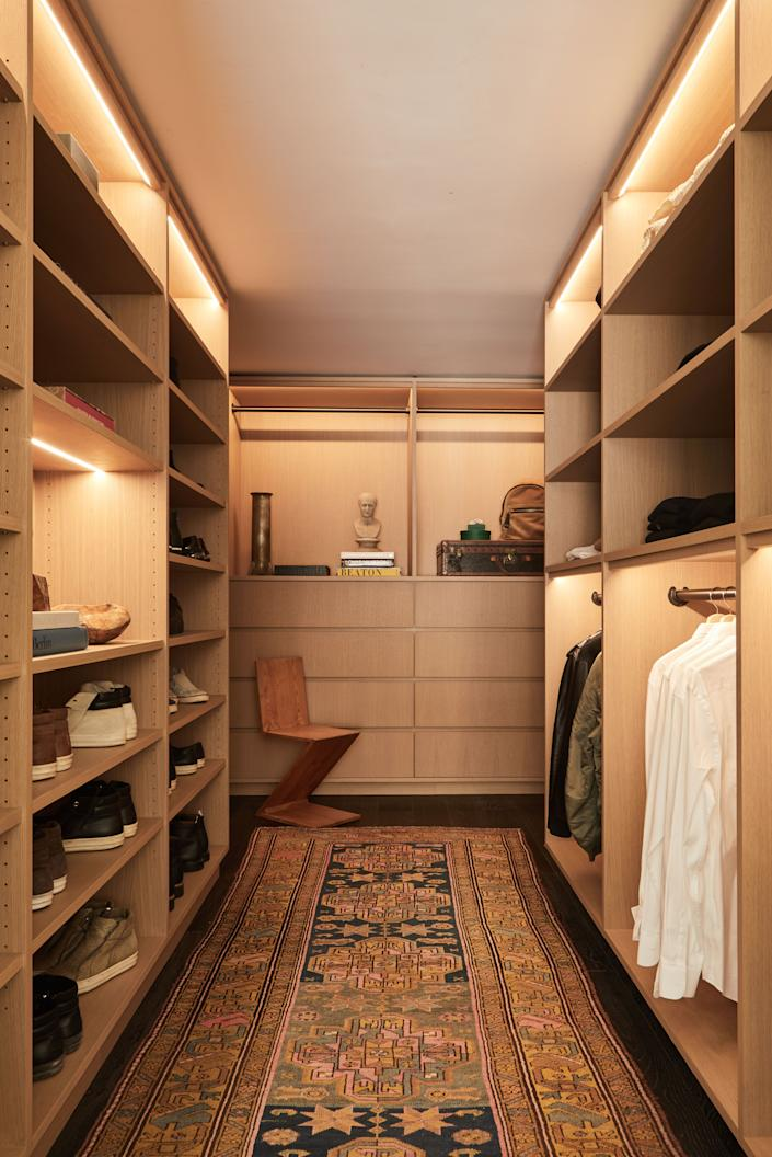 """<div class=""""caption""""> A few pieces of furniture and accessories—such as the Zig Zag chair by Gerrit Rietveld, the cast bronze vase by Rick Owens, the cast marble bust of a man, and the vintage Isfahan Persian handmade wool and silk rug—adorn the walk-in closet, making it both functional and stylish. </div>"""