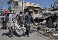 <p>Men carry the body of 24-year-old Sergeline Joseph after they were paid by her father Thomas Silvain, rear left, more than US$200 to retrieve her from the rubble of their collapsed house instead of waiting for demolition crews, in Port-au-Prince, Tuesday, Feb. 2, 2010. (Photo: Andres Leighton/AP) </p>