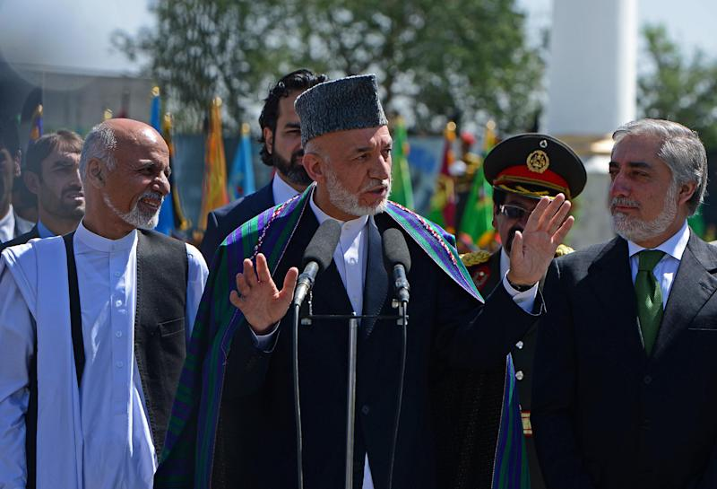 Afghan President Hamid Karzai (C) gestures while speaking as presidential candidates Ashraf Ghani (L) and Abdullah Abdullah (R) look on in Kabul on August 19, 2014 (AFP Photo/Wakil Kohsar)