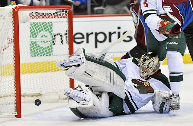 Minnesota Wild goalie Darcy Kuemper, bottom, lets the puck slip past for a Colorado Avalanche goal by Jamie McGinn in the first period during Game 7 of an NHL hockey first-round playoff series on Wednesday, April 30, 2014, in Denver. (AP Photo/Jack Dempsey)