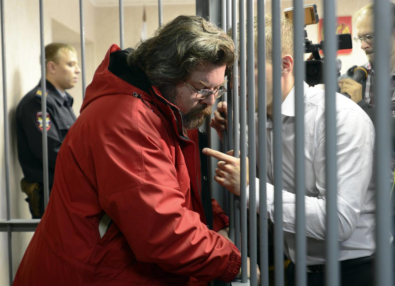 Greenpeace International spokesperson Roman Dolgov speaks to an unidentified man from inside a defendants' box at a district court building in Murmansk, September 26, 2013. Russian President Vladimir Putin said on Wednesday that the activists had violated international law but signalled they should not face charges of piracy. Russian authorities seized the activists' ship, the Arctic Sunrise, and towed it to shore after two of the activists tried to scale the rig to protest against Russian plans to drill for oil in the Arctic, which they say poses a threat to the fragile eco-system. REUTERS/Stringer (RUSSIA - Tags: CRIME LAW ENERGY BUSINESS)