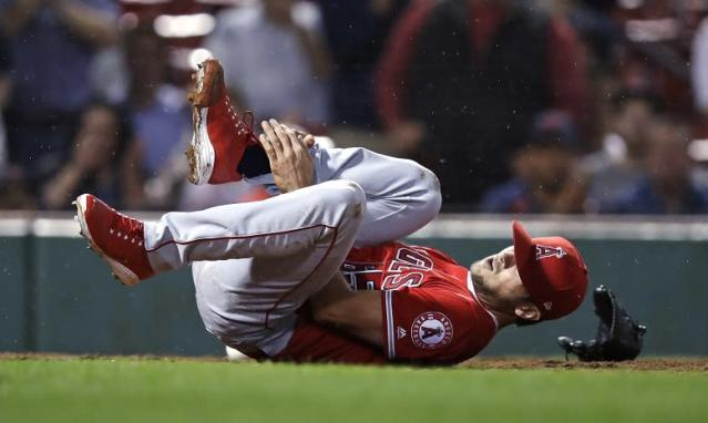 Los Angeles Angels' pitcher Jake Jewell rolls on the field after injuring his right ankle while covering home during Wednesday's game in Boston. (AP)