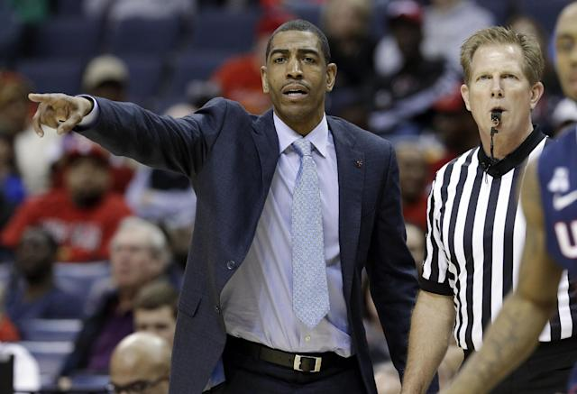 Connecticut coach Kevin Ollie gestures as he and an official watch during the second half of an NCAA college basketball game between Connecticut and Cincinnati in the semifinals of the American Athletic Conference men's tournament Friday, March 14, 2014, in Memphis, Tenn. (AP Photo/Mark Humphrey)