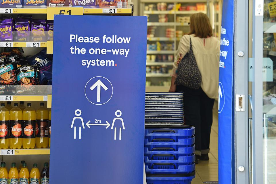 A sign instructing shoppers to maintain social distancing is seen at the entrance to a Tesco supermarket in Lincoln, Eastern England on April 20, 2020, as life in Britain continues during the nationwide lockdown to combat the novel coronavirus pandemic. - The number of people in England who have died in hospital from coronavirus has risen by 429 to 14,929 according to daily health ministry figures on Monday, April 20. (Photo by Oli SCARFF / AFP) (Photo by OLI SCARFF/AFP via Getty Images)