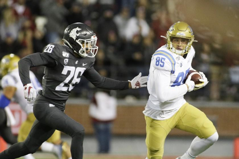 UCLA tight end Greg Dulcich runs with the ball while under pressure by Washington State safety Bryce Beekman.