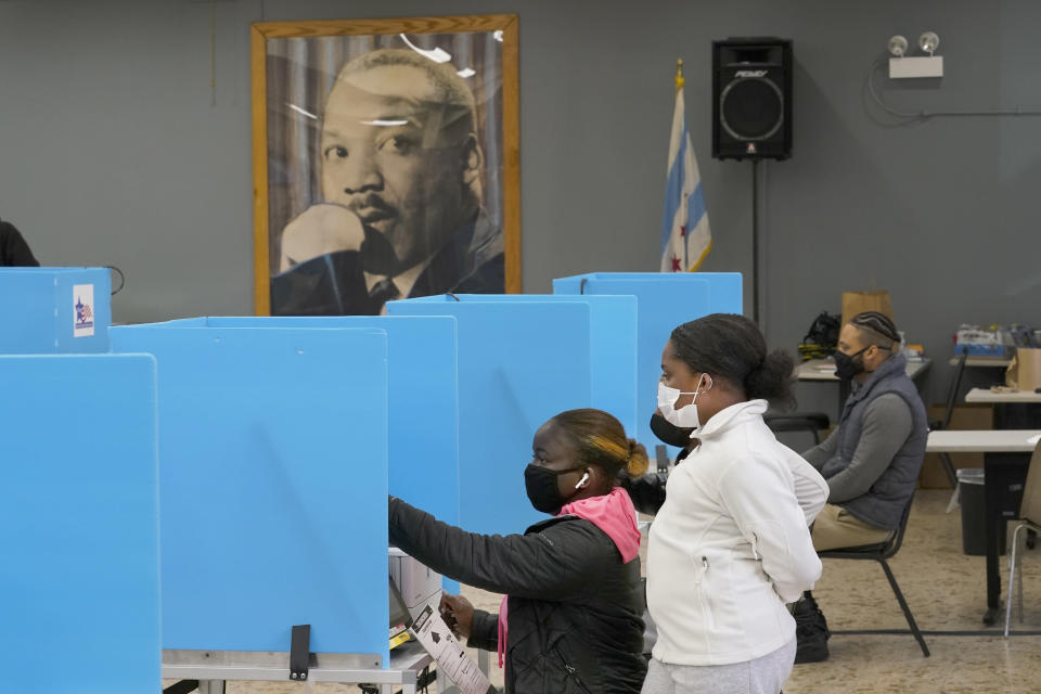 Jeniya Garrett, right, watches her aunt Catherina Neal vote on Election Day, Tuesday, Nov. 3, 2020, at the Dr. Martin Luther King Community Center in the Bronzeville neighborhood of Chicago. (AP Photo/Charles Rex Arbogast)