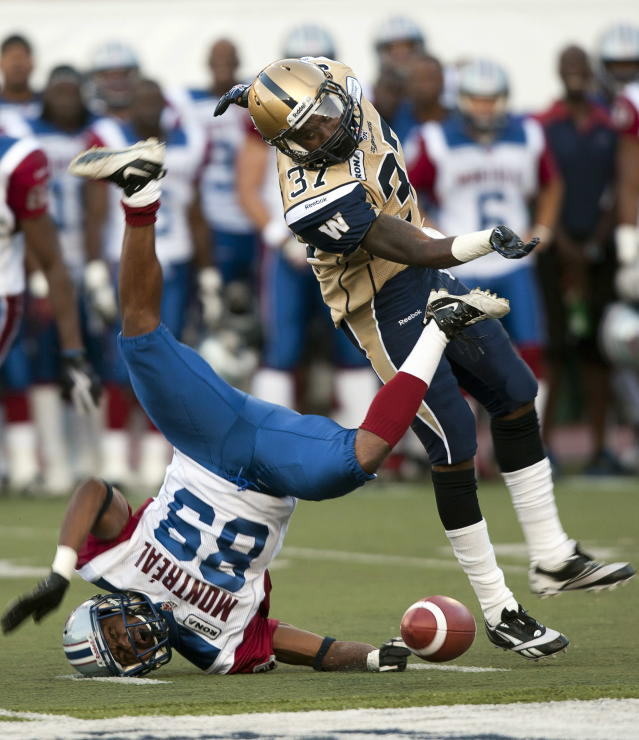 Montreal Alouettes receiver Travon Patterson, left, is tackled by Winnipeg Blue Bombers Demond Washington during first quarter Canadian Football League pre-season action Thursday, June 14, 2012 in Montreal. THE CANADIAN PRESS/Ryan Remiorz