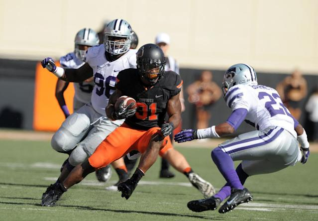 Oklahoma State running back Jeremy Smith (31), attempts to run past Kansas State defensive back Dante Barnett (23), while being pursued by defensive lineman Chaquil Reed (98) during the first half of an NCAA college football game in Stillwater, Okla., Saturday, Oct. 5, 2013. (AP Photo/Brody Schmidt)