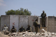 Israeli soldiers rest at the site of a vehicle attack near Hizmeh Junction in the West Bank, Wednesday, June 16, 2021. The Israeli military on Wednesday shot and killed a Palestinian woman who it said tried to ram her car into a group of soldiers guarding a West Bank construction site. (AP Photo/Maya Alleruzzo)