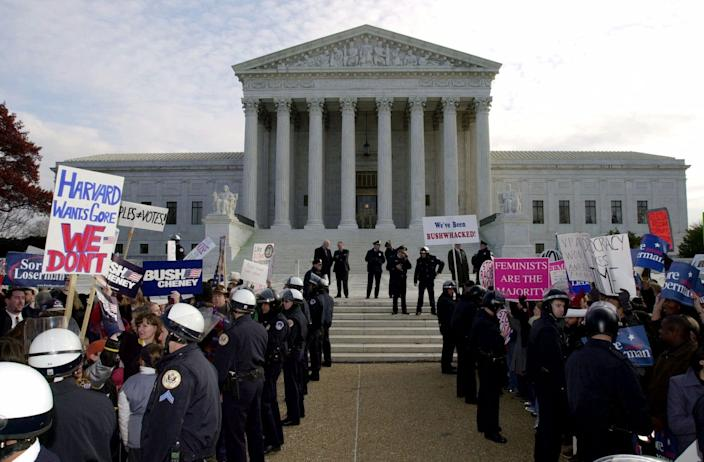 Police separate the supporters of George W. Bush, left, and the supporters of Al Gore, right, in front of the Supreme Court on Dec. 1, 2000.