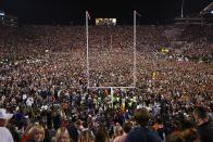 FILE - Fans rush the field after Auburn defeated Alabama in the Iron Bowl NCAA college football game, Saturday, Nov. 25, 2017, in Auburn, Ala. College football fans will head back into stadiums this weekend, and along with binoculars, sunscreen and other essentials, some will pack facemasks and proof of vaccination. Alabama and Auburn are in a state with one of the lowest vaccination rates in the country and rabid fan bases. Neither have announced stadium screenings or mask requirements. (AP Photo/Brynn Anderson, File)