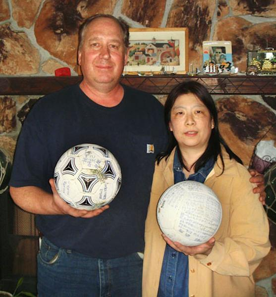 In this April 21, 2012 photo released by The Baxters via Kyodo News, David and Yumi Baxter hold a soccer ball and a volleyball which David found, at their house in the suburbs of Anchorage, Alaska. Kyodo News agency says the teenage owner of the soccer ball that apparently floated across the Pacific Ocean after last year's tsunami is surprised and thankful the ball - which had his name written on it - was found in Alaska. (AP Photo/The Baxters via Kyodo News) JAPAN OUT, MANDATORY CREDIT, NO LICENSING IN CHINA, HONG KONG, JAPAN, SOUTH KOREA AND FRANCE